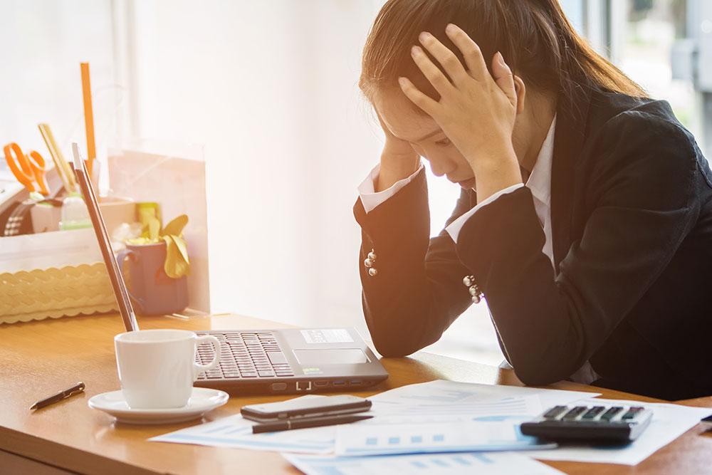 ストレスで頭を抱えるスーツ姿の女性