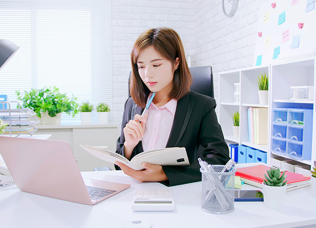 ノートを見ながら考えるスーツ姿の女性